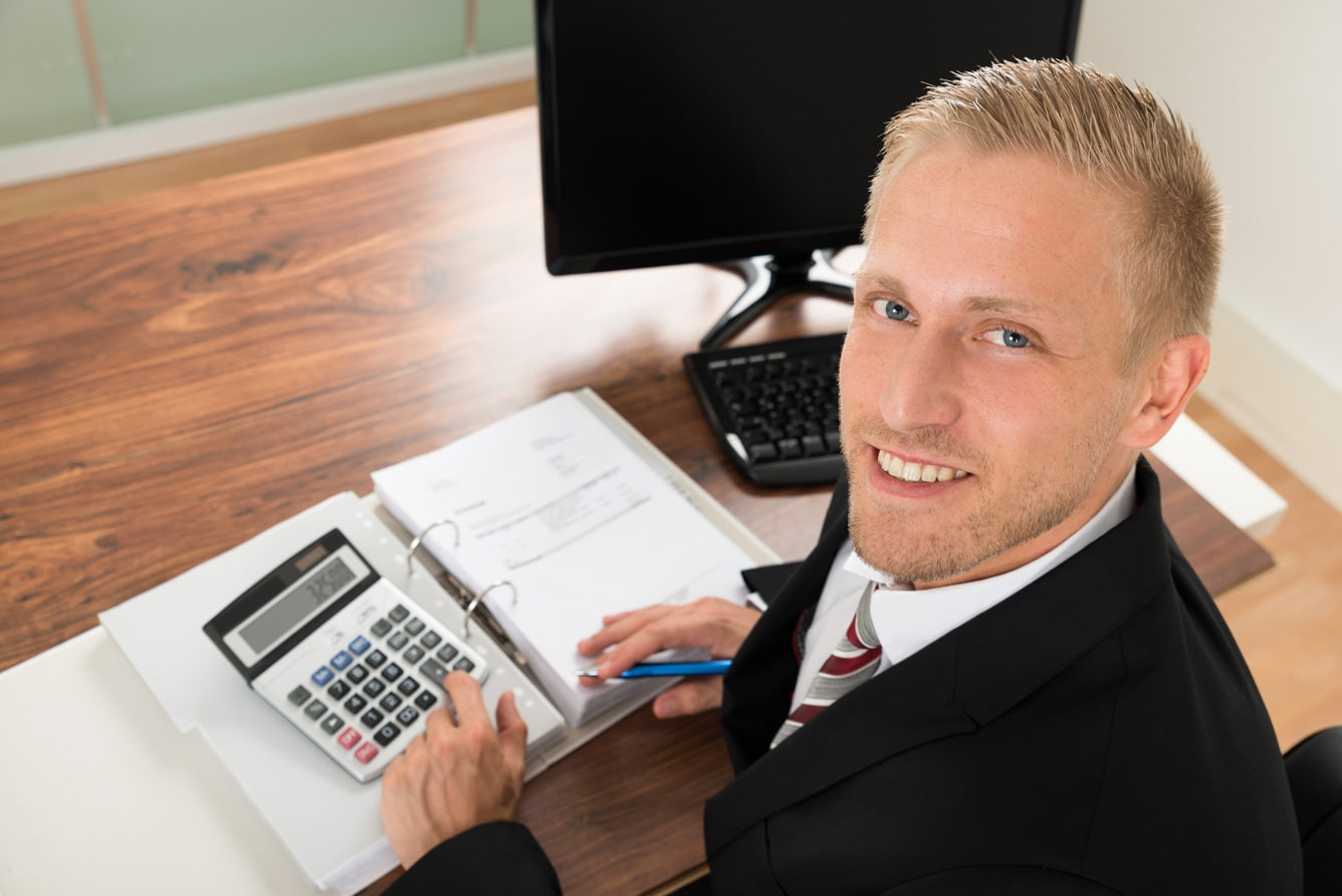 happy-businessman-calculating-finance-in-office