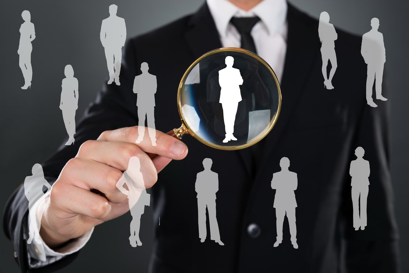 midsection-of-businessman-searching-candidate-with-magnifying-glass-over-gray-background
